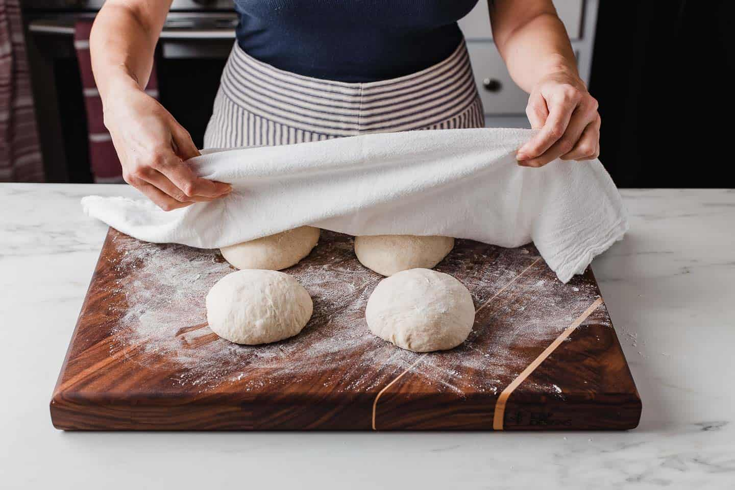 A woman covering sourdough pizza dough with a flour towel.