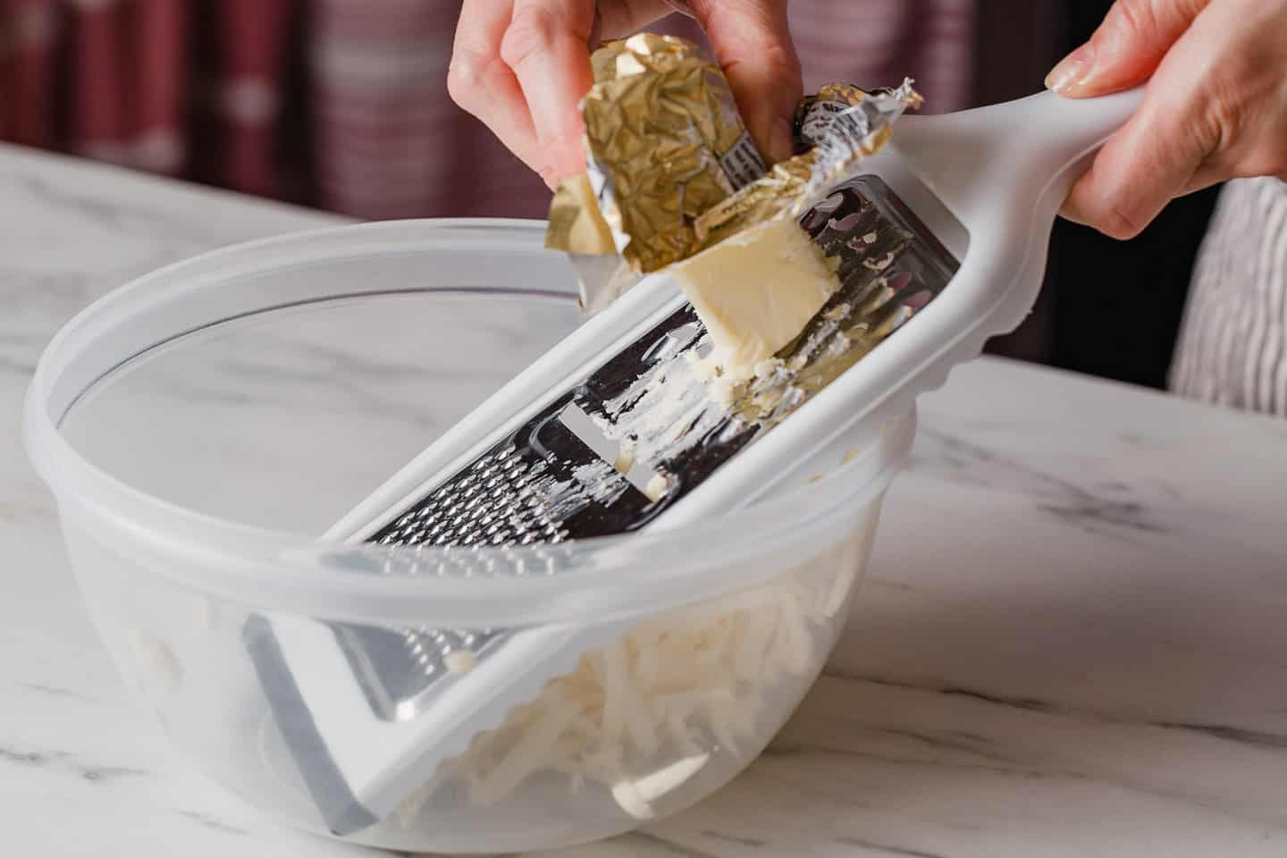 A woman grating butter into a bowl.