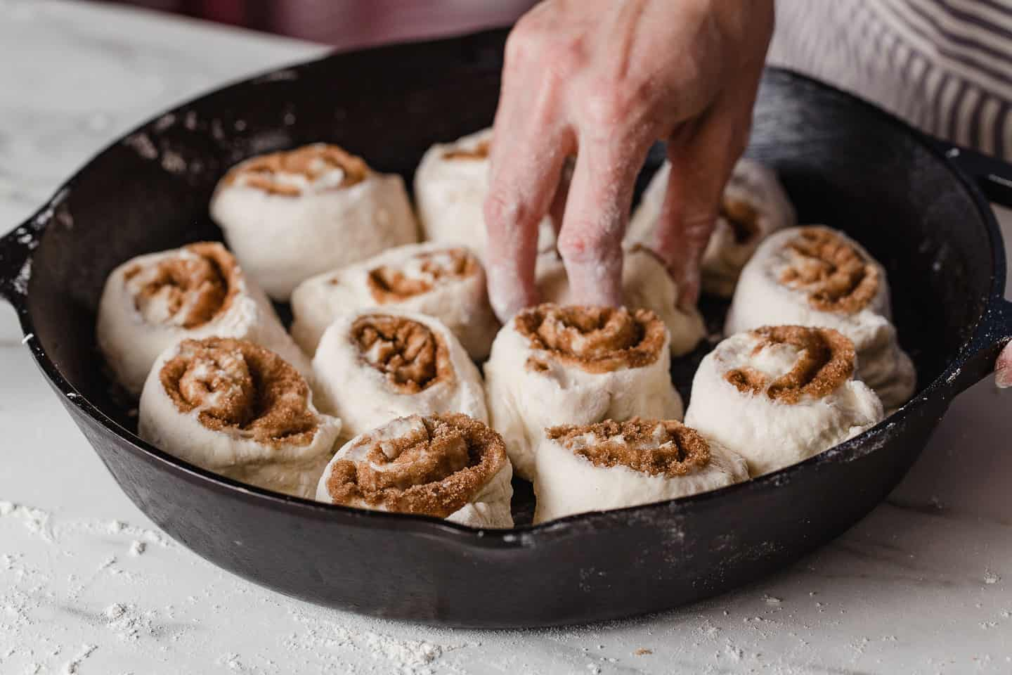 A woman placing unbaked cinnamon roll dough into a cast iron skillet.