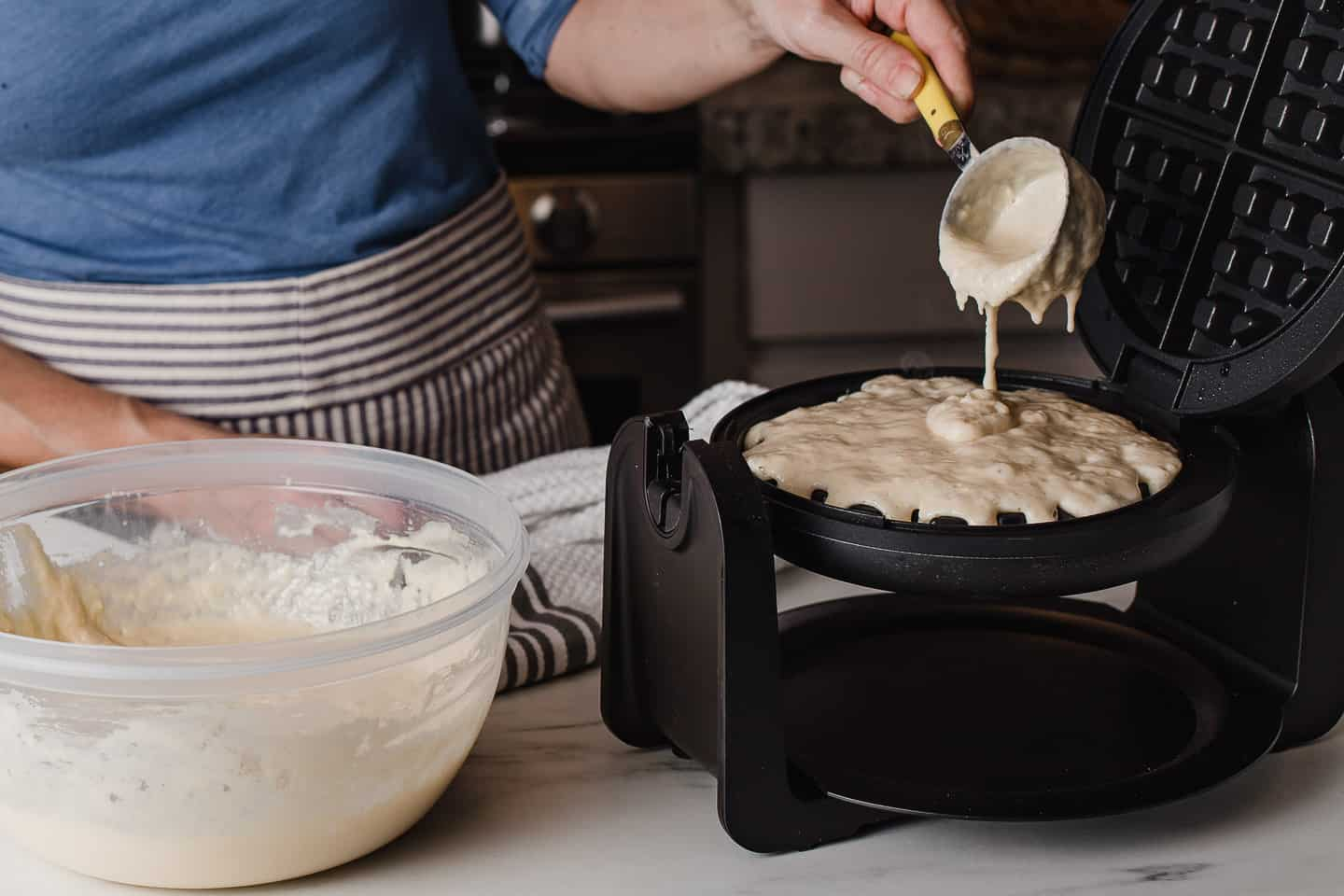 A woman pouring waffle batter onto a hot griddle.