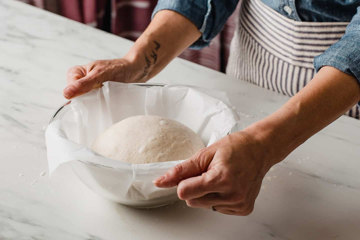 A woman placing a shaped dough ball into a bowl to proof.