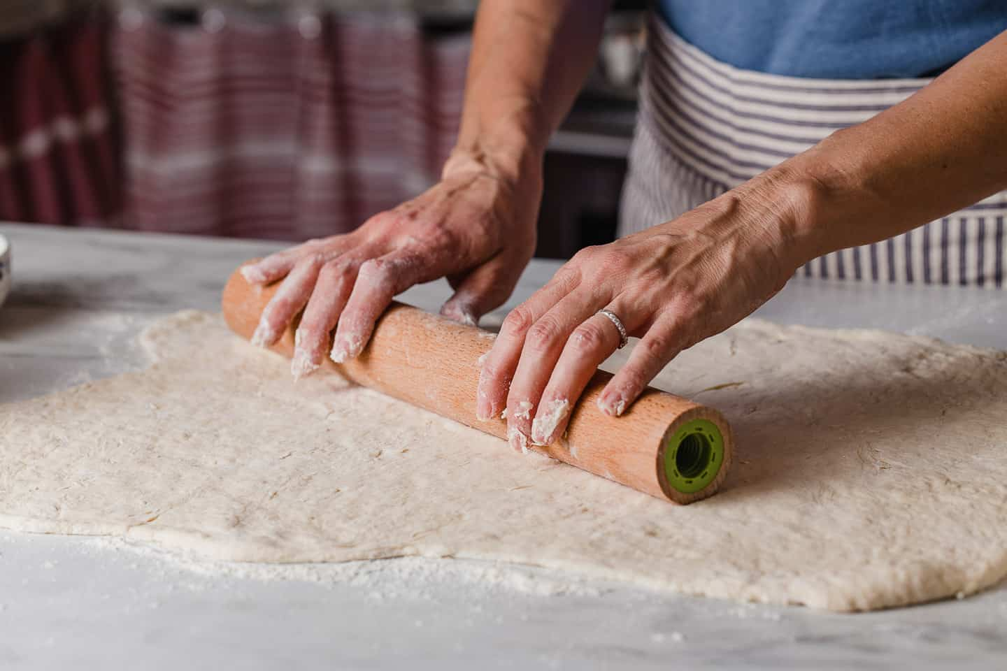 A woman rolling out cinnamon roll dough with a rolling pin.