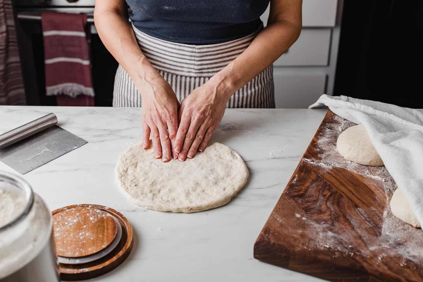 A woman shaping a sourdough pizza crust.