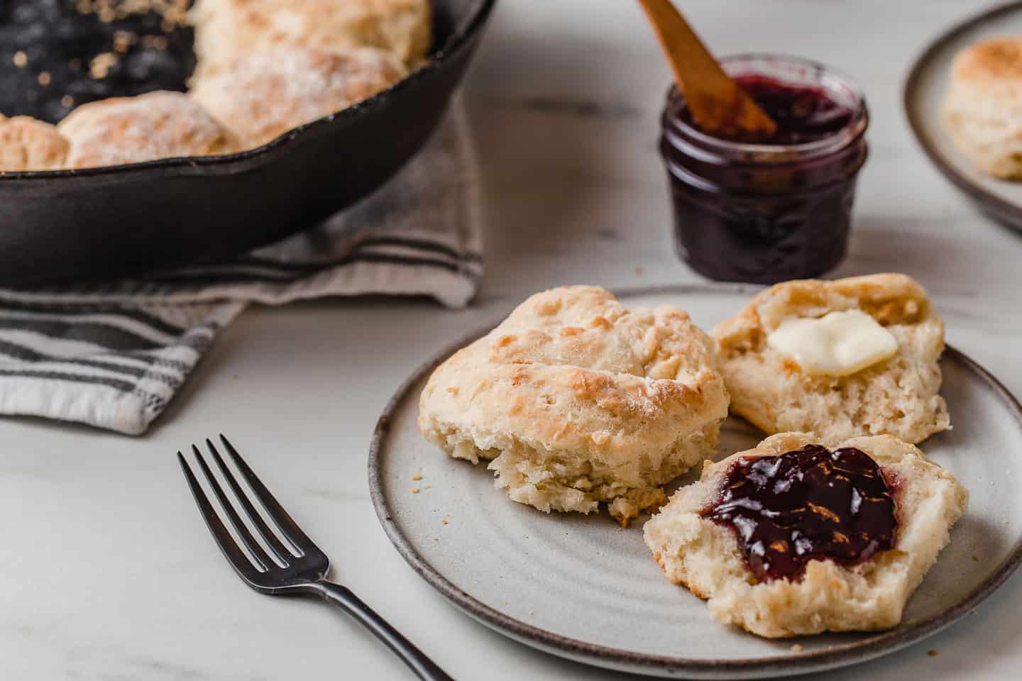 A plate of sourdough biscuits with preserves and butter.