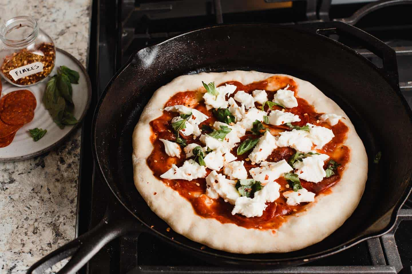 A cast iron skillet on the stove with pizza crust and toppings.