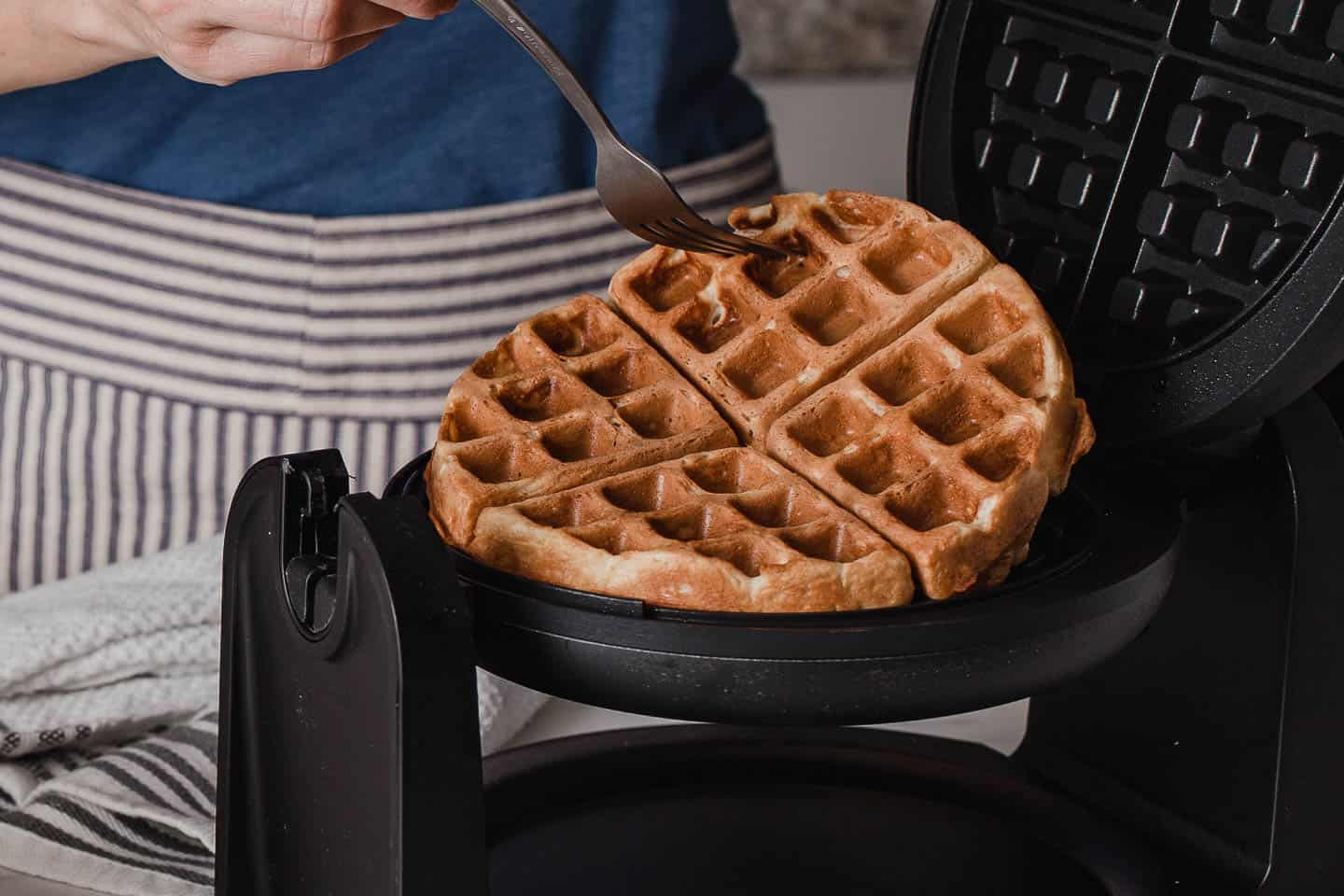 A waffle being removed from a griddle.