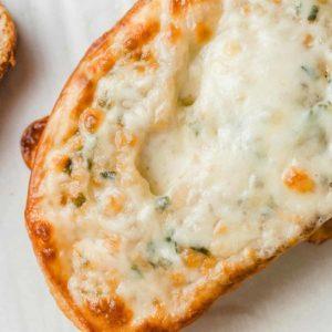 A closeup photograph of cheesy garlic bread.