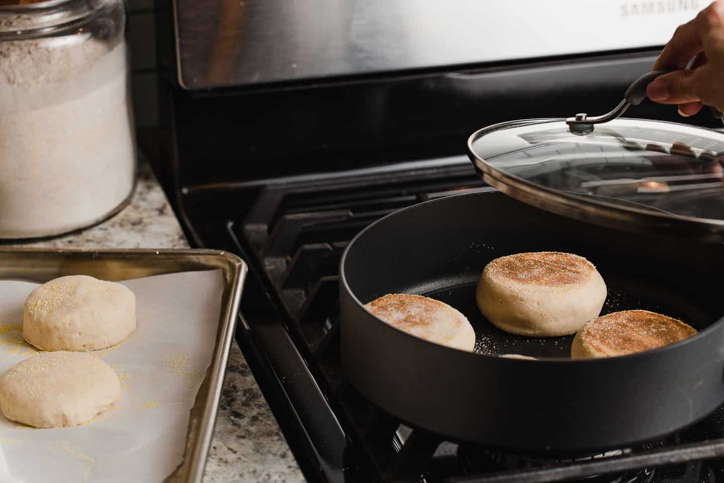 Sourdough english muffins cooking in a skillet.