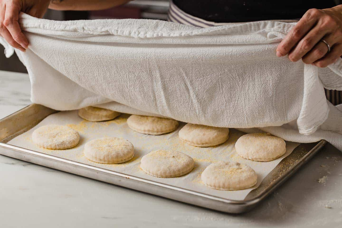 A woman covering sourdough english muffins with a tea towel.