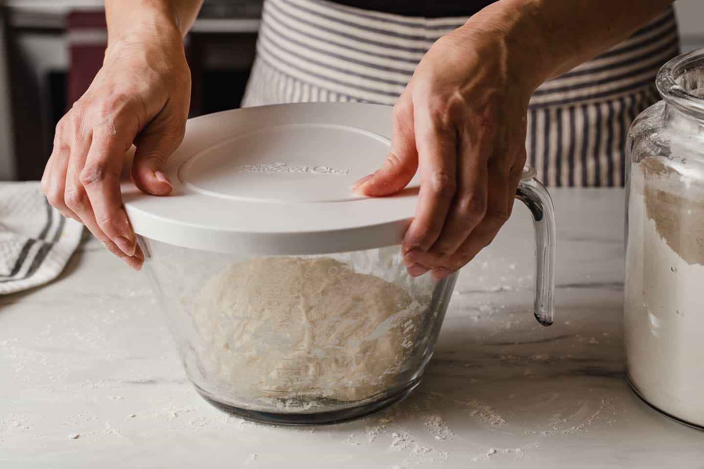 A woman placing a cover on a bowl of dough.