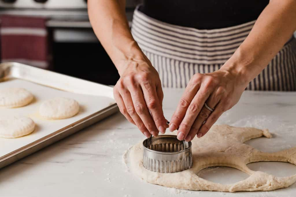 A woman cutting out sourdough english muffins with a biscuit cutter.