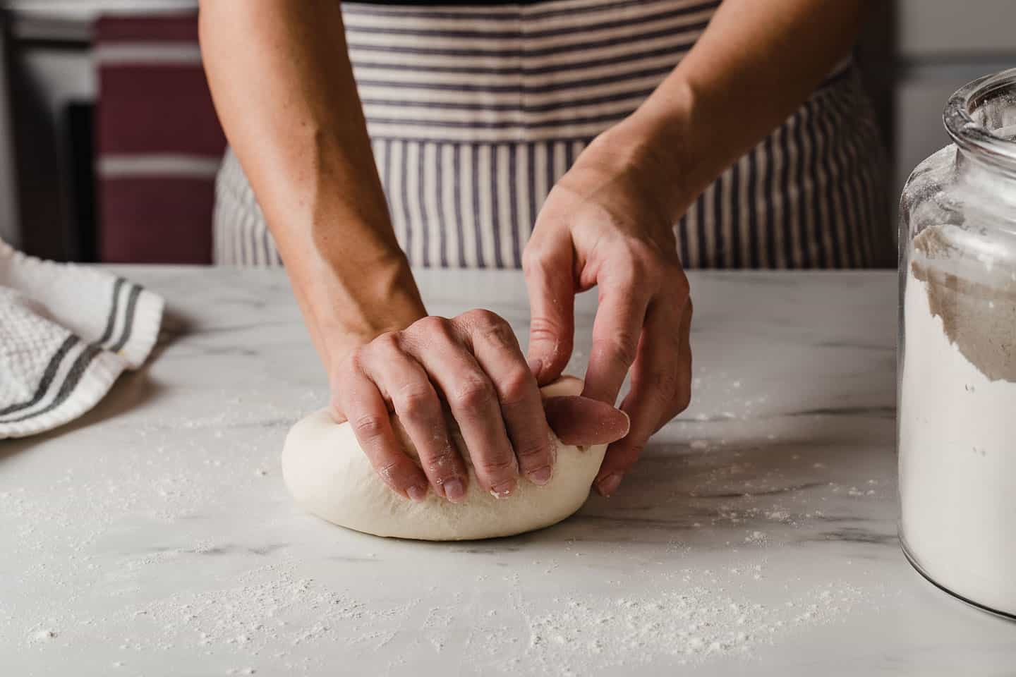 A woman kneading sourdough english muffins dough.