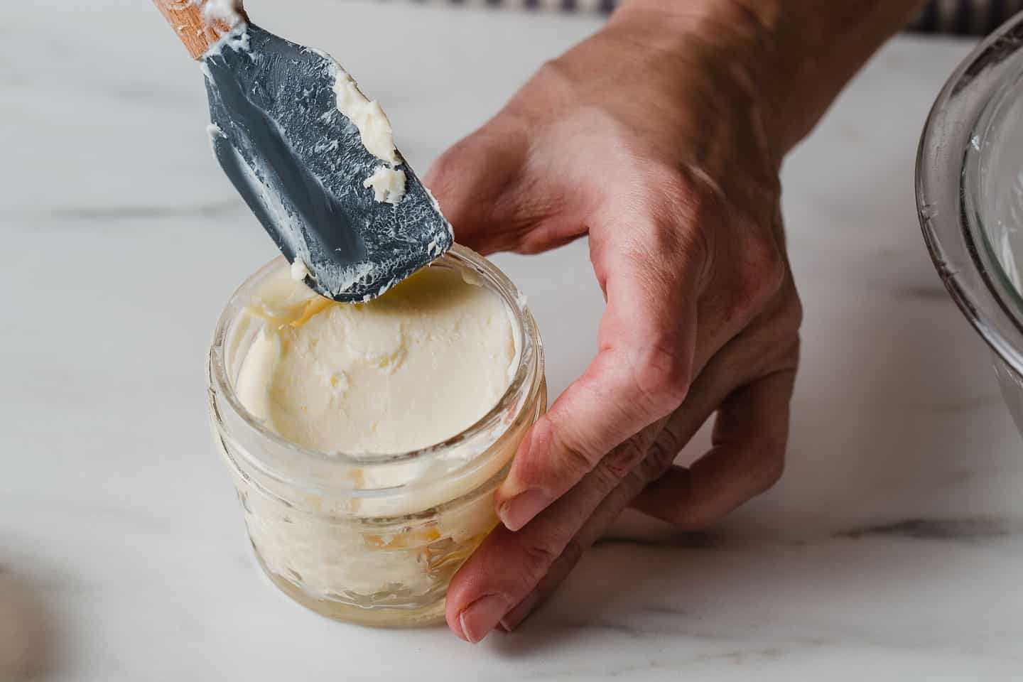 A lady putting homemade butter into a glass jar.