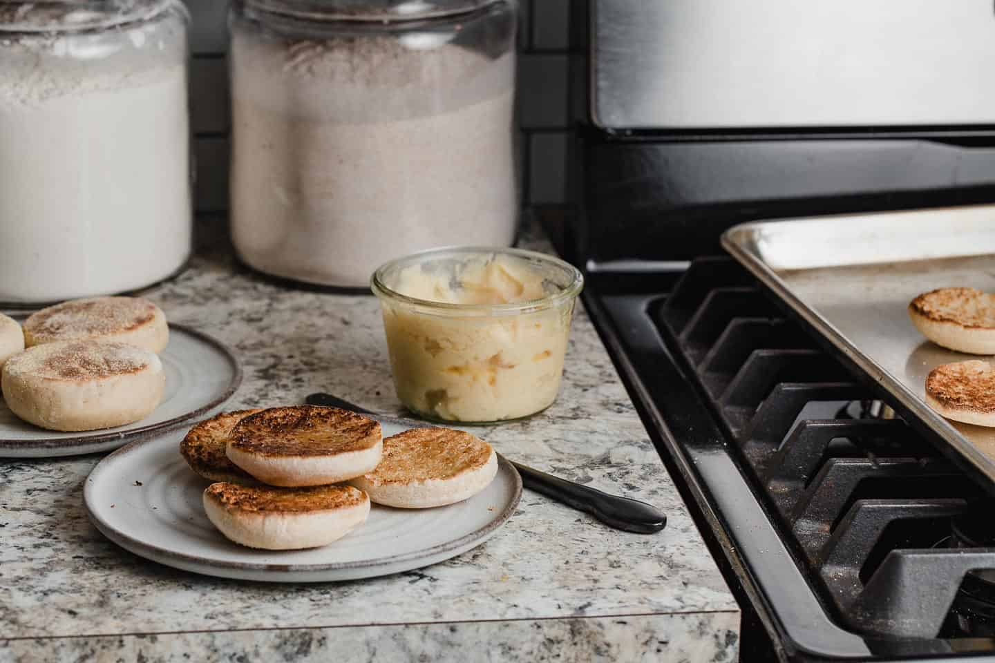 A plate of english muffins on a kitchen counter with butter next to a stove.