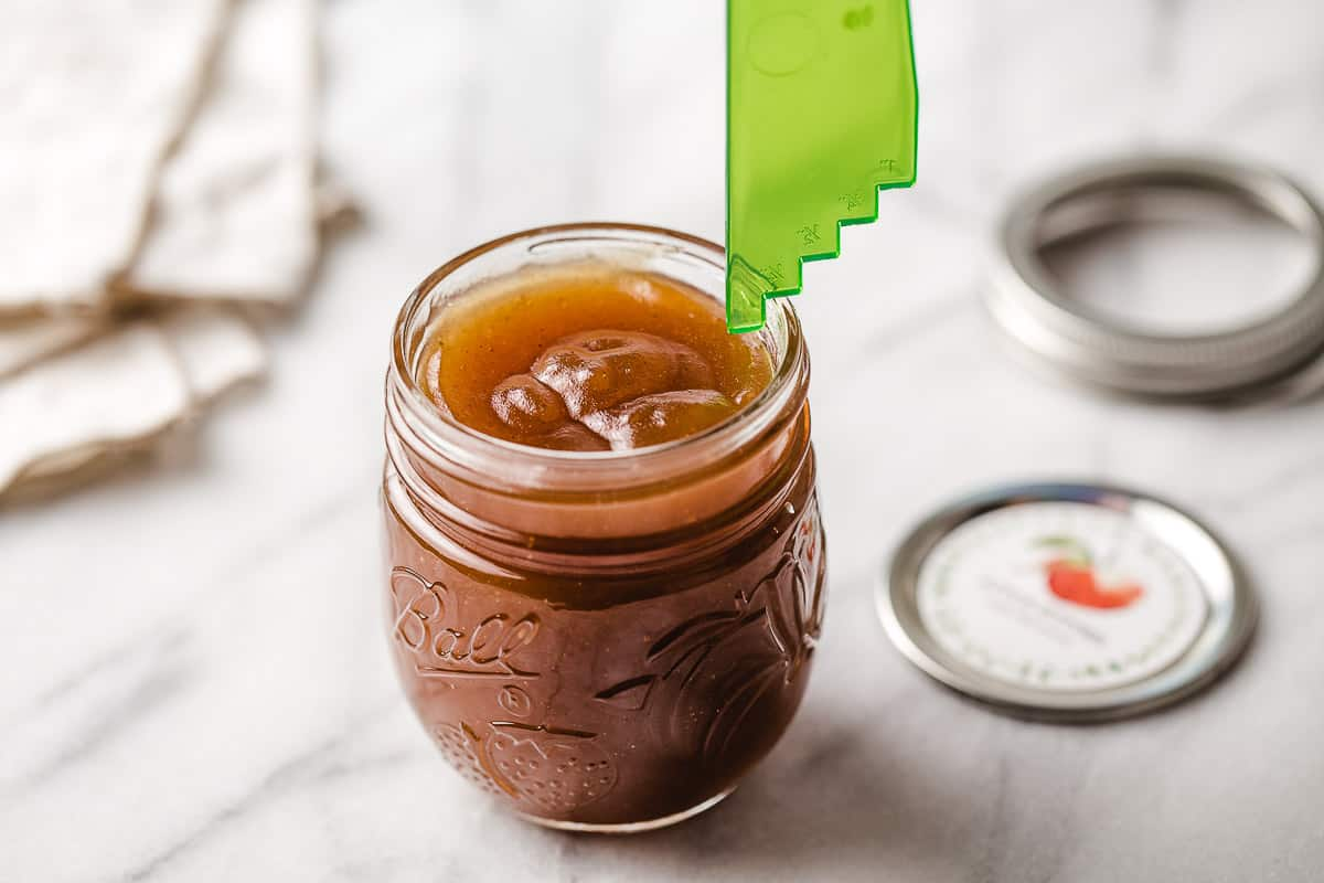 Headspace being measured in a jar of apple butter.