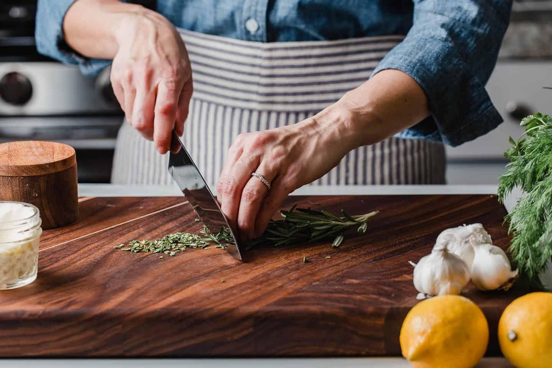 A woman cutting fresh rosemary on a cutting board.