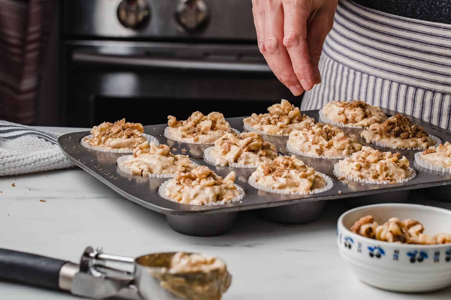 A woman sprinkling walnuts on top of sourdough banana nut muffins.