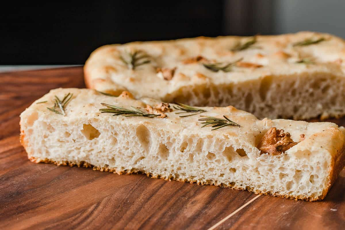 A picture showing the open crumb inside a slice of focaccia bread.