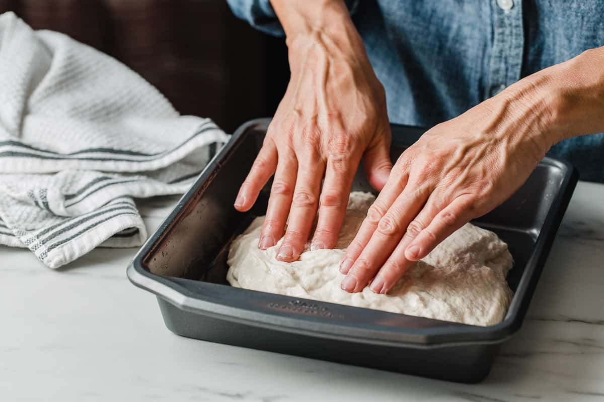 A woman pressing focaccia dough into a baking dish.