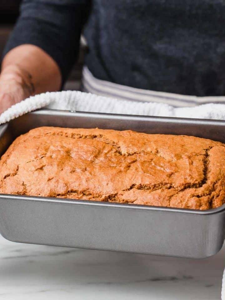 A woman holding a loaf of sourdough pumpkin bread.