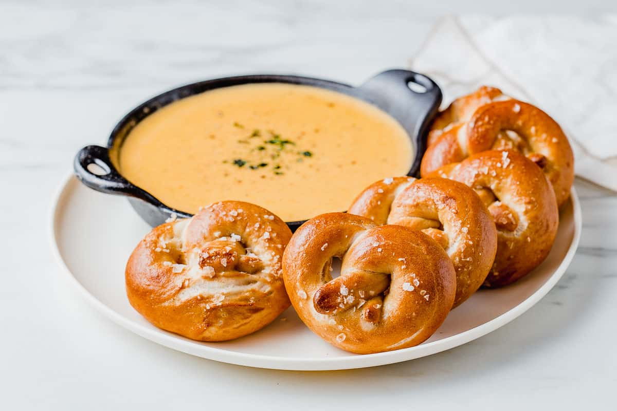 Sourdough pretzels on a plate with beer cheese dip.