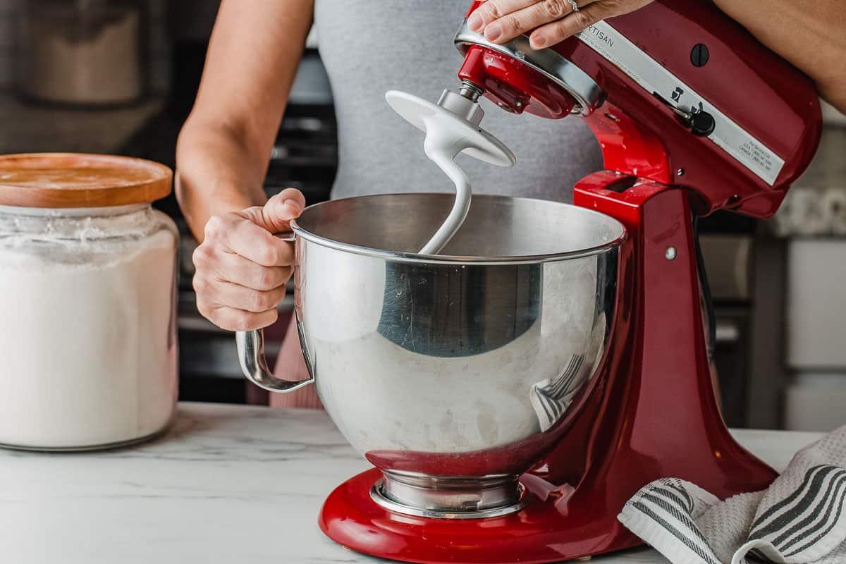 A woman using a stand mixer to knead sourdough pretzel dough.