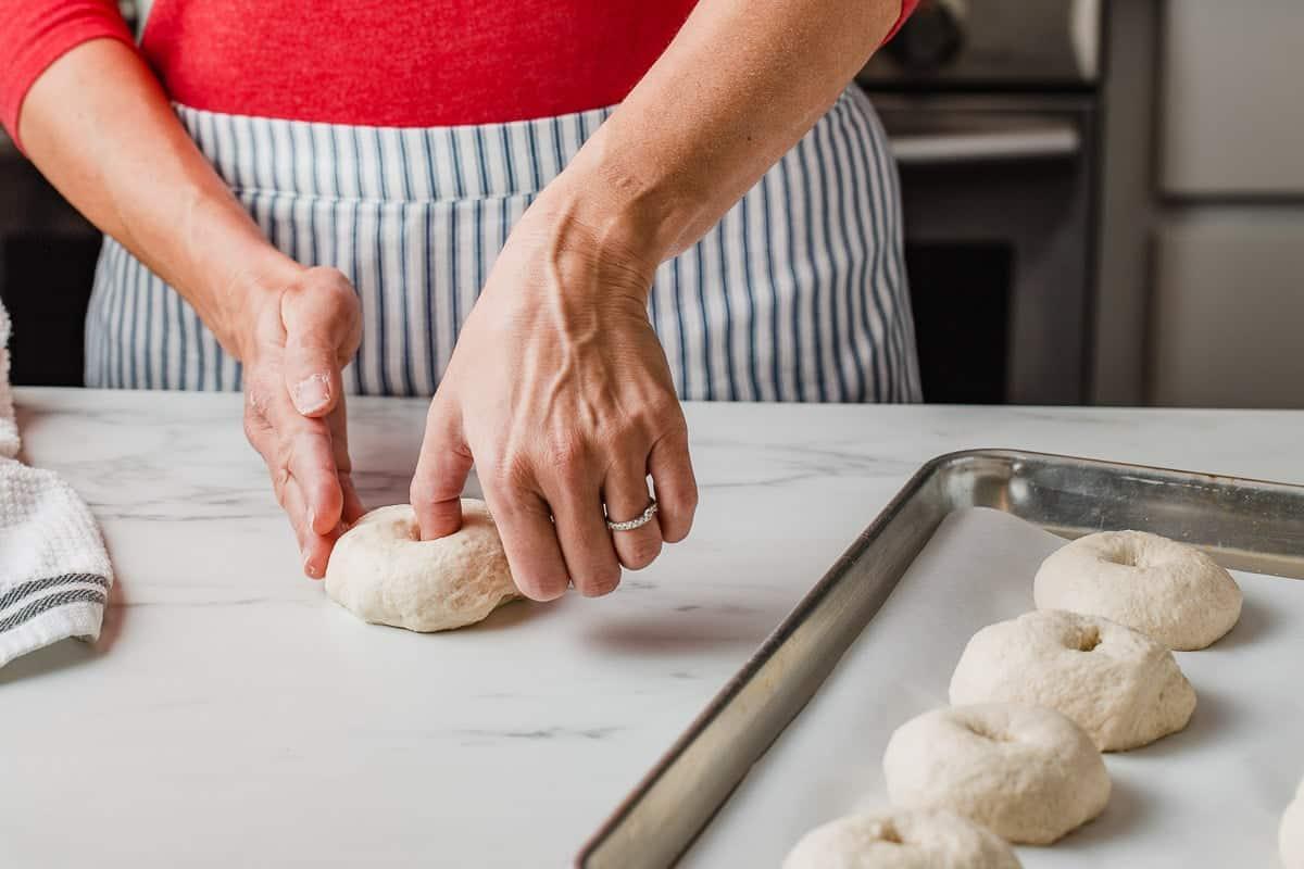 A woman shaping sourdough bagels.