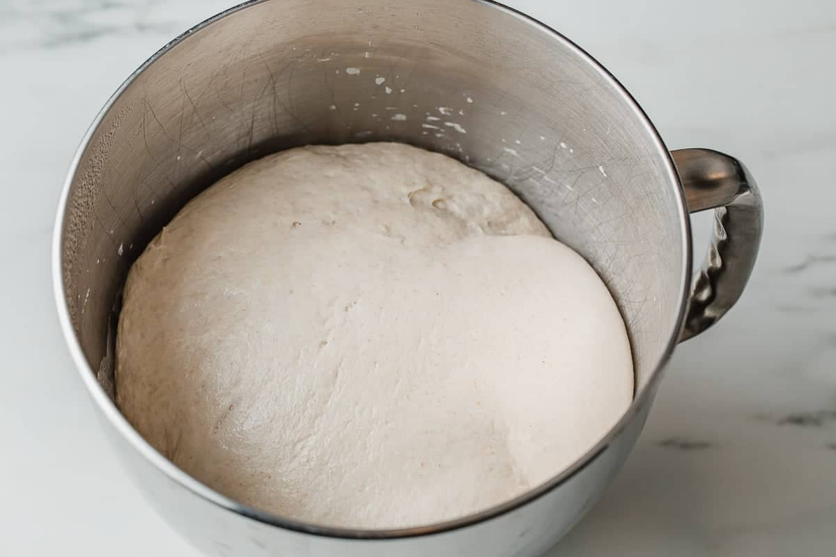 Proved dough in the bowl of a stand mixer.