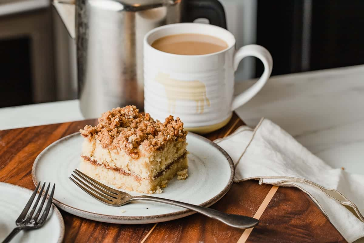 A slice of coffee cake on a plate with a cup of coffee.