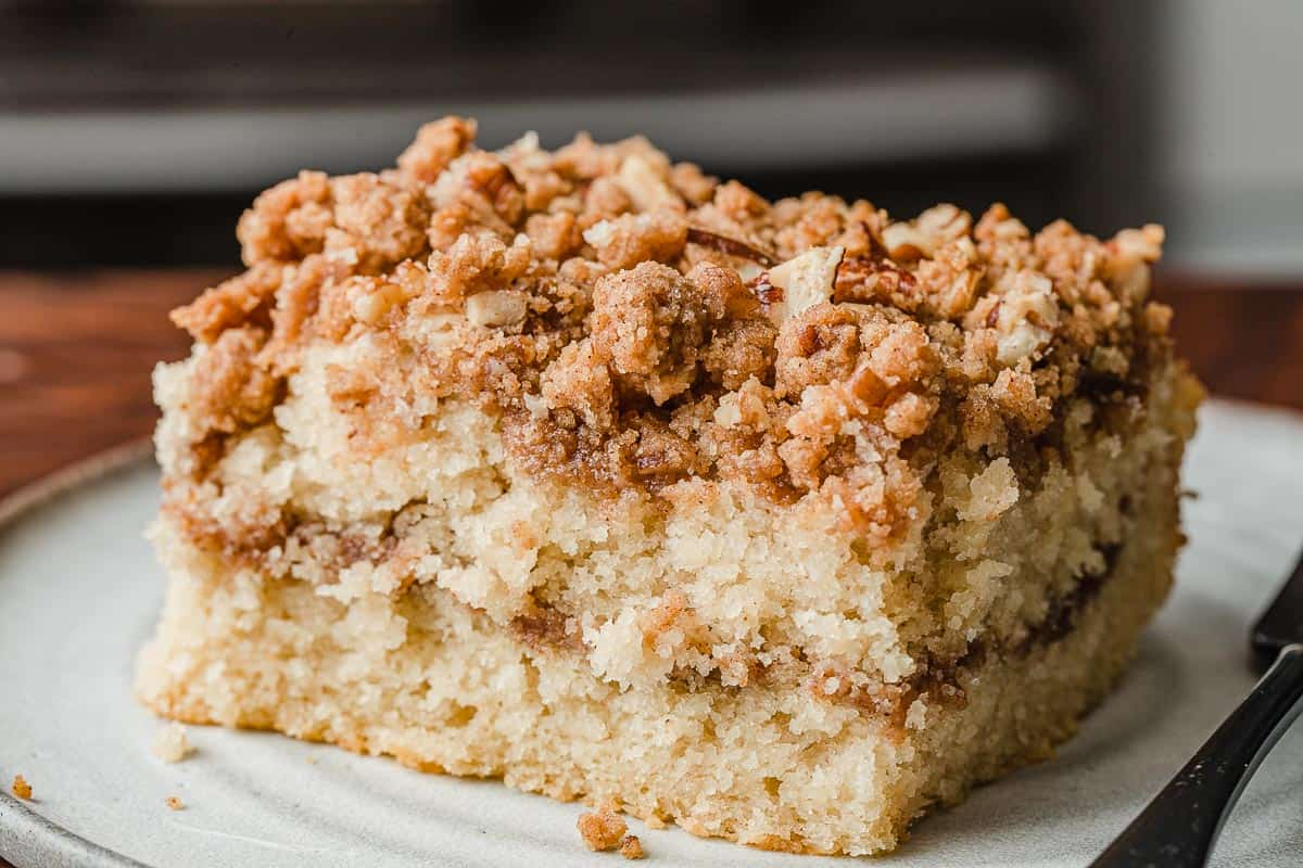 A slice of sourdough coffee cake on a plate with a fork.