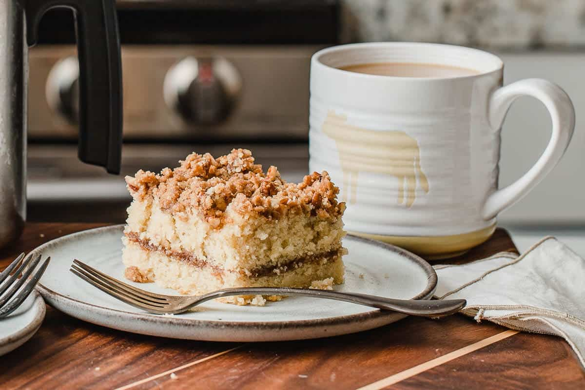 Sourdough coffee cake on a plate next to a cup of coffee.