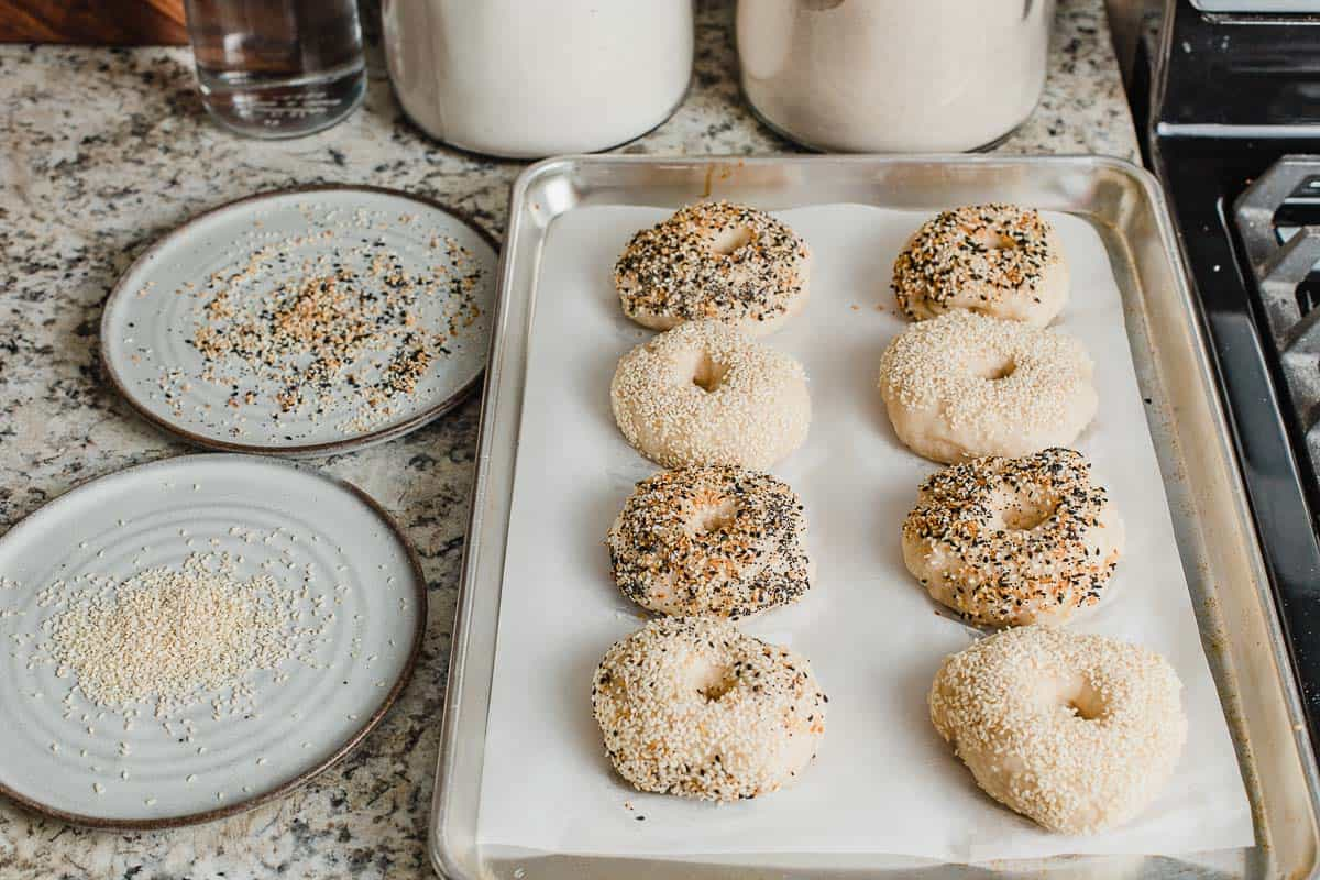 A tray of boiled bagels with toppings.