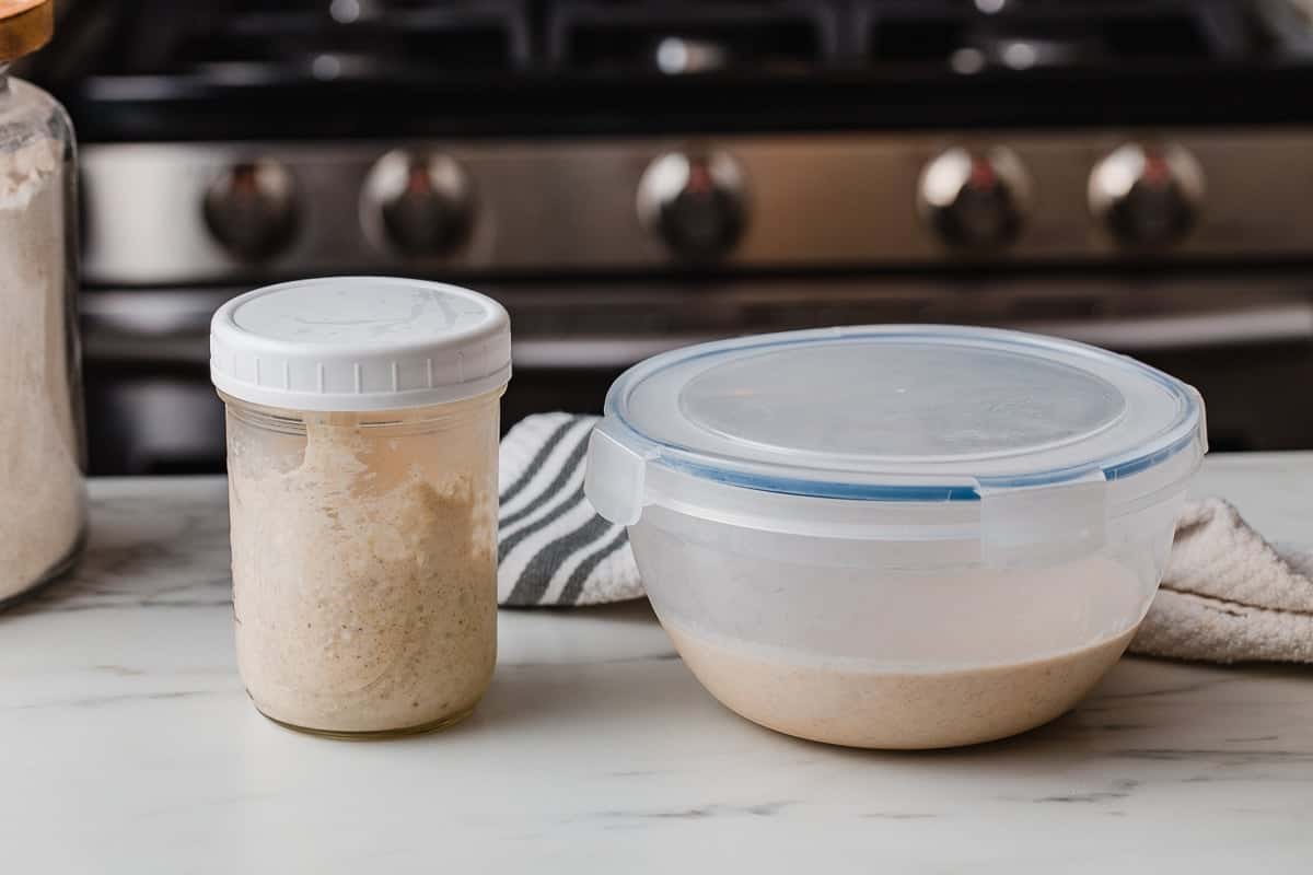 A jar of starter and container of discarded starter on a kitchen counter.