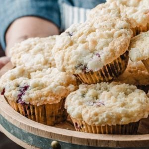 A woman holding a tray of sourdough blueberry muffins.