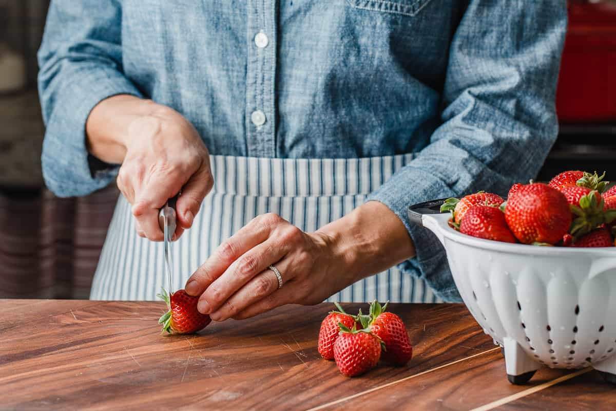 A woman cutting strawberries.