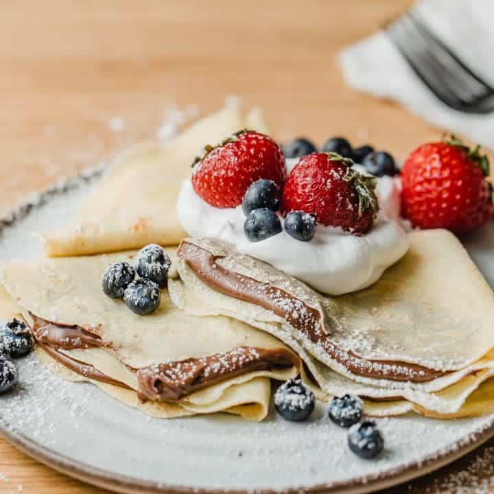 Sourdough crepes on a plate with nutella and berries.