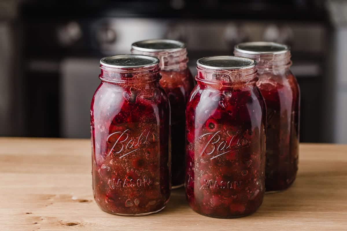 Four quart sized jars with blueberry pie filling.