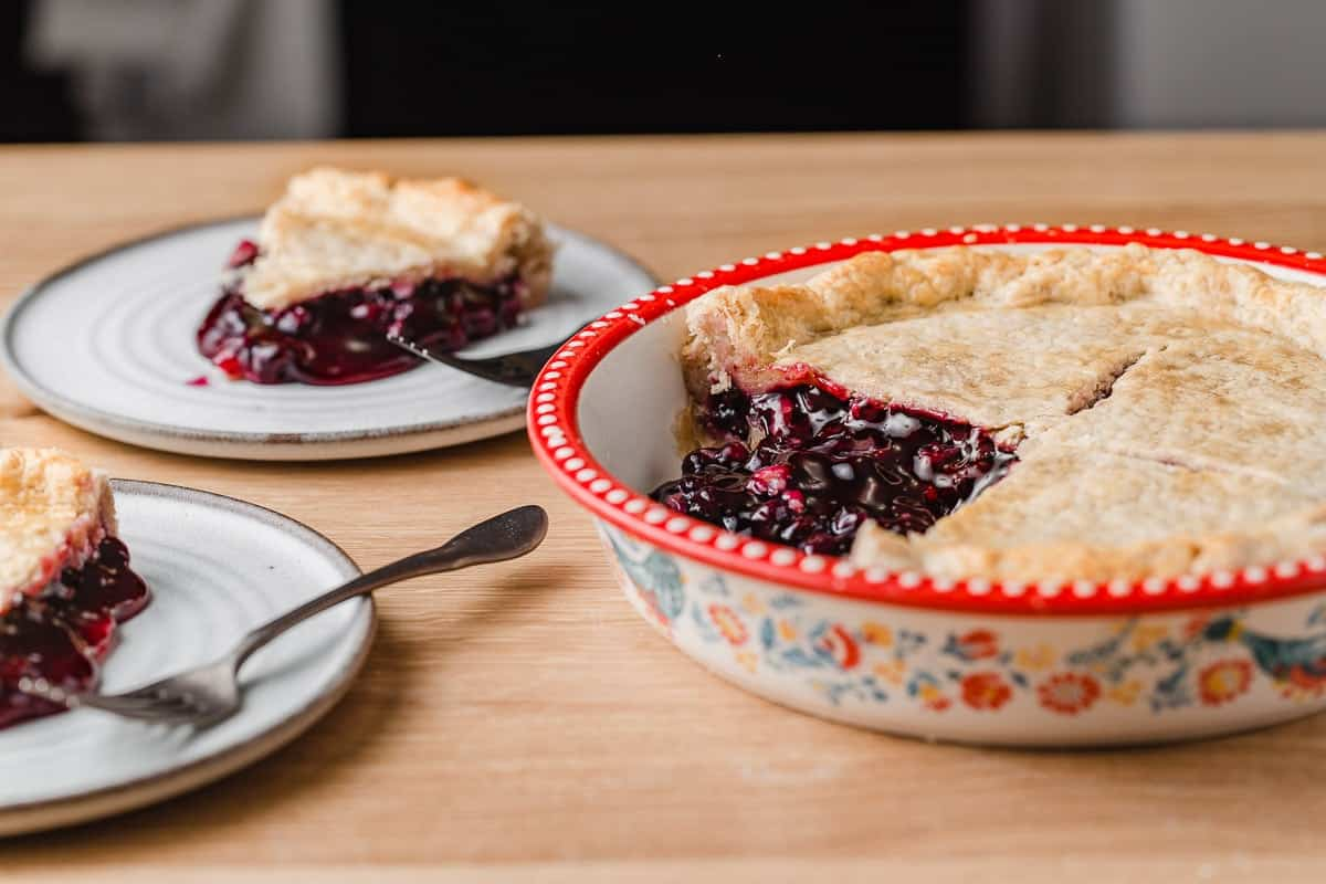 A baked blueberry pie with 2 slices on  plates.