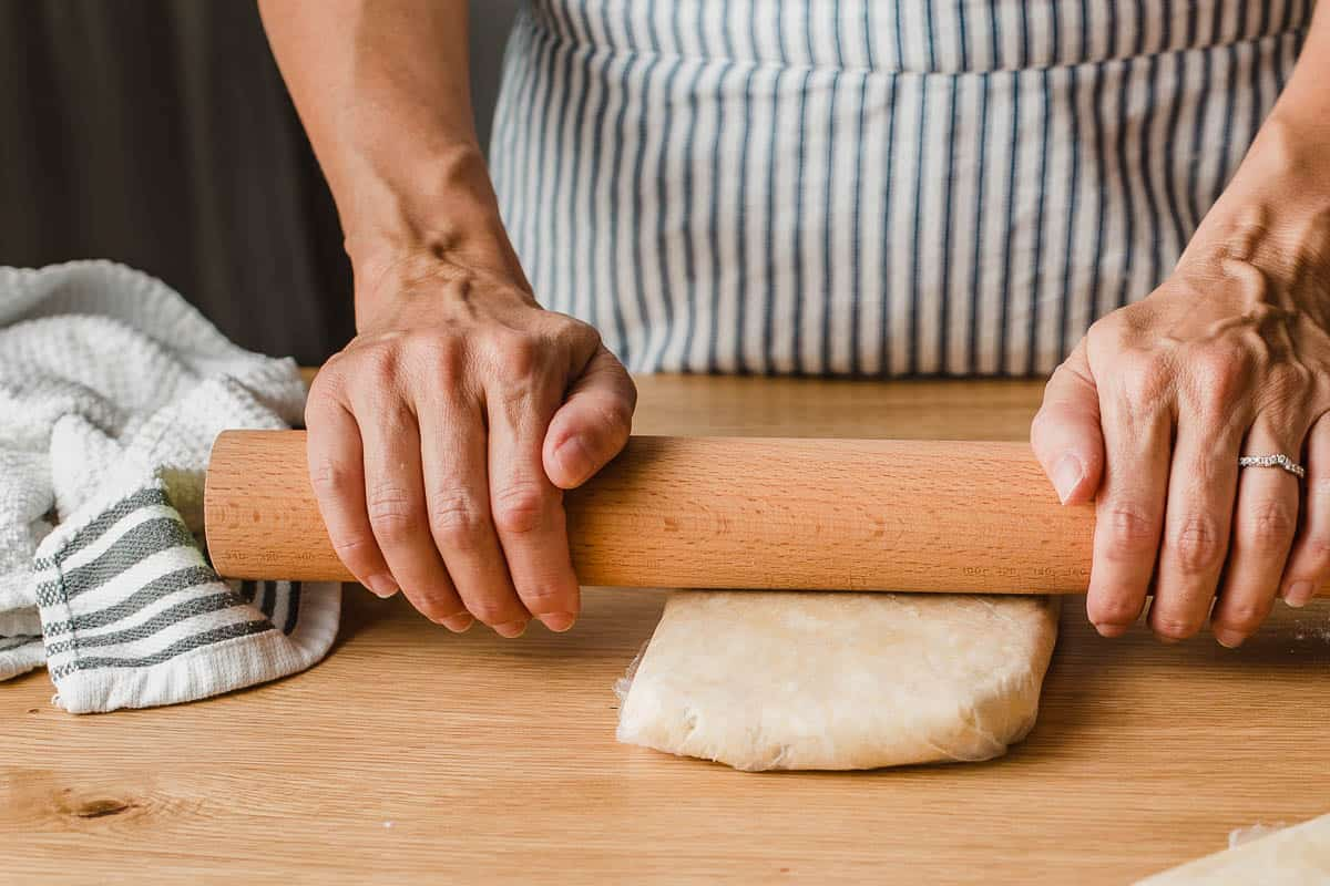 A woman rolling dough in plastic wrap.