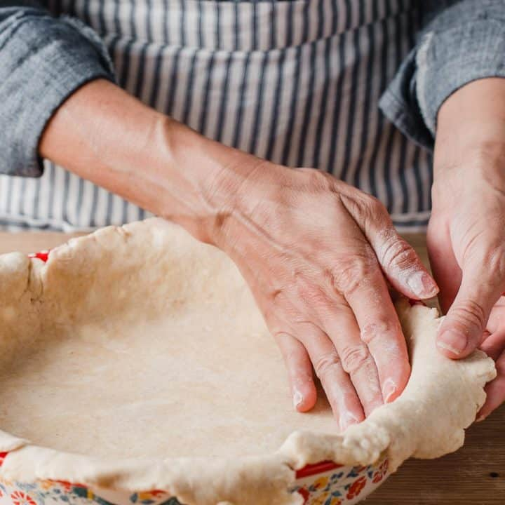 A woman pressing a pie crust into a pie plate.