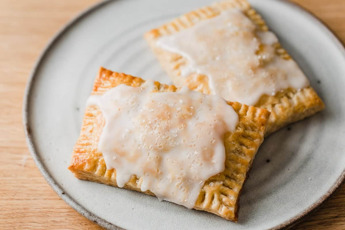 Two glazed pop tarts on a plate.