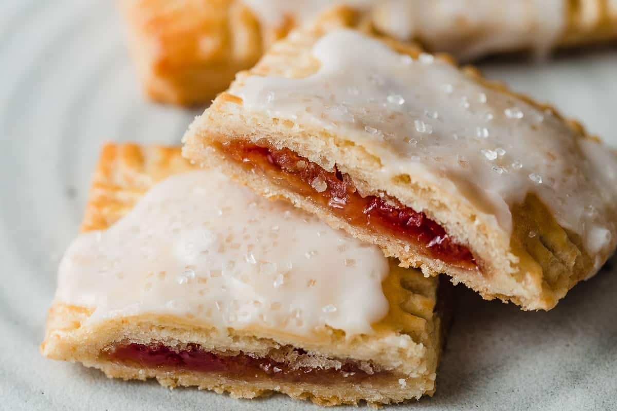 A strawberry sourdough pop tart cut in half on a plate.