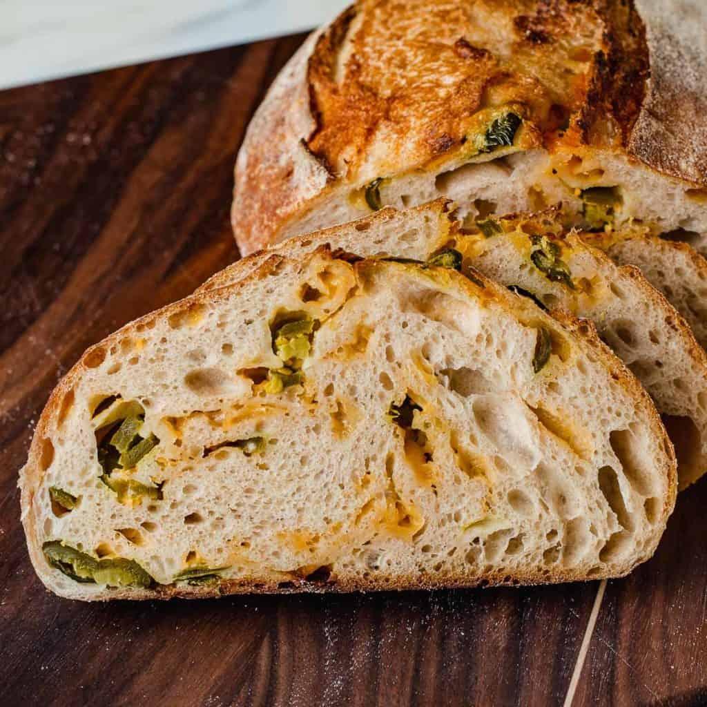 A slice of jalapeno cheddar sordough bread on a cutting board.