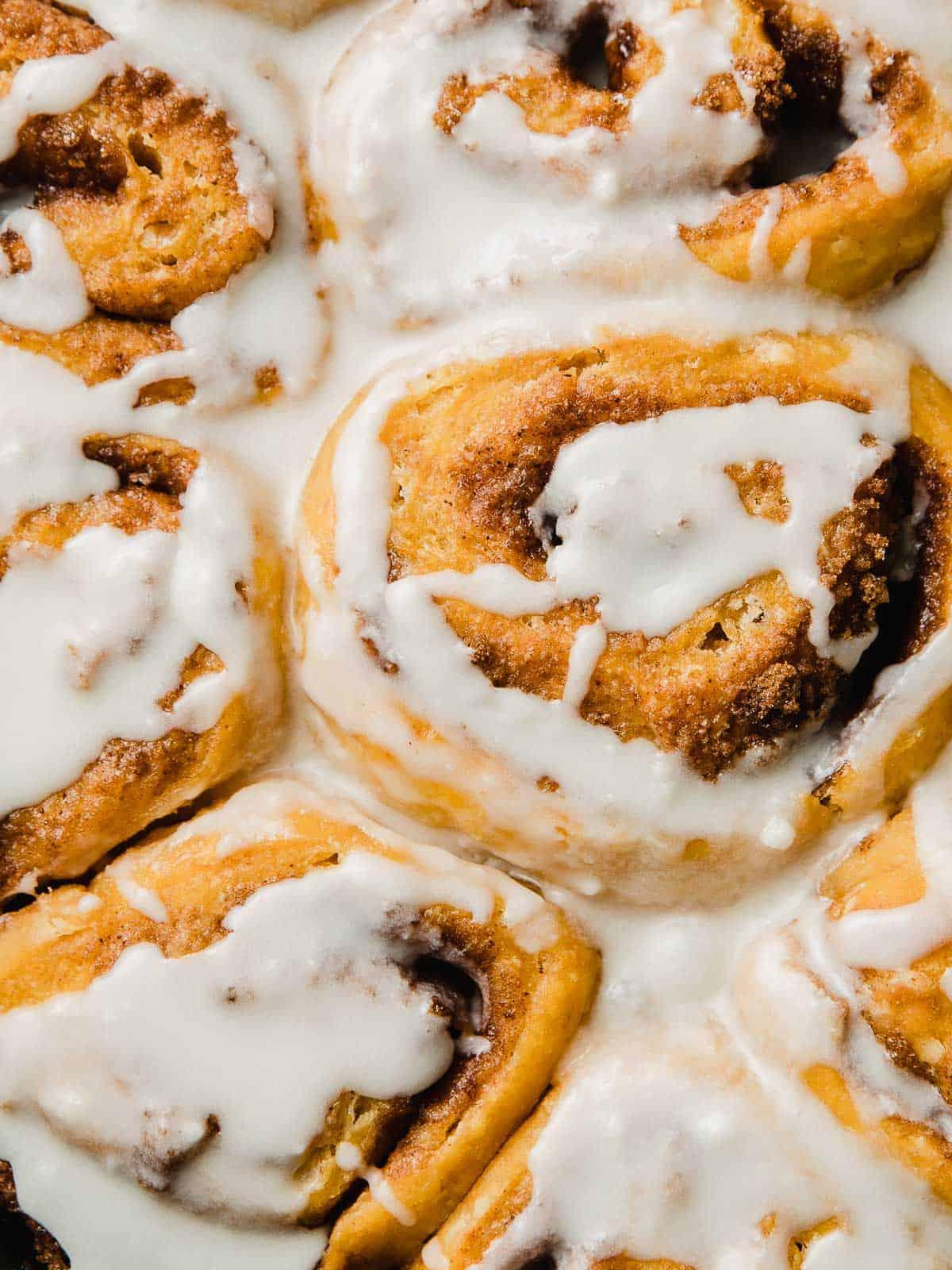 A closeup photograph of glazed sourdough pumpkin cinnamon rolls.
