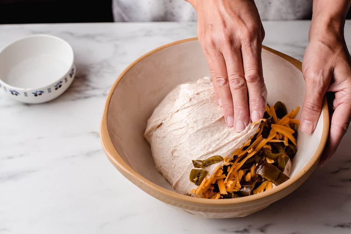 A woman folding cheddar into sourdough.