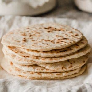 A stack of sourdough tortillas on a plate.