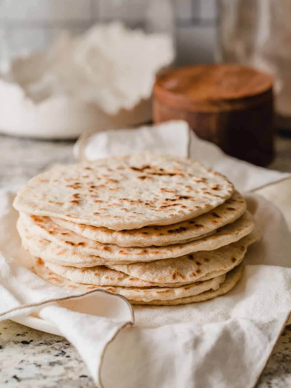 Sourdough tortillas in a stack on a counter.