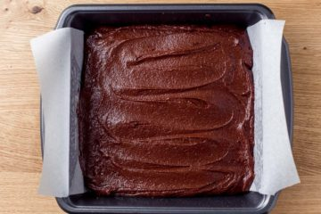 Brownie batter in a baking dish lined with parchment paper.
