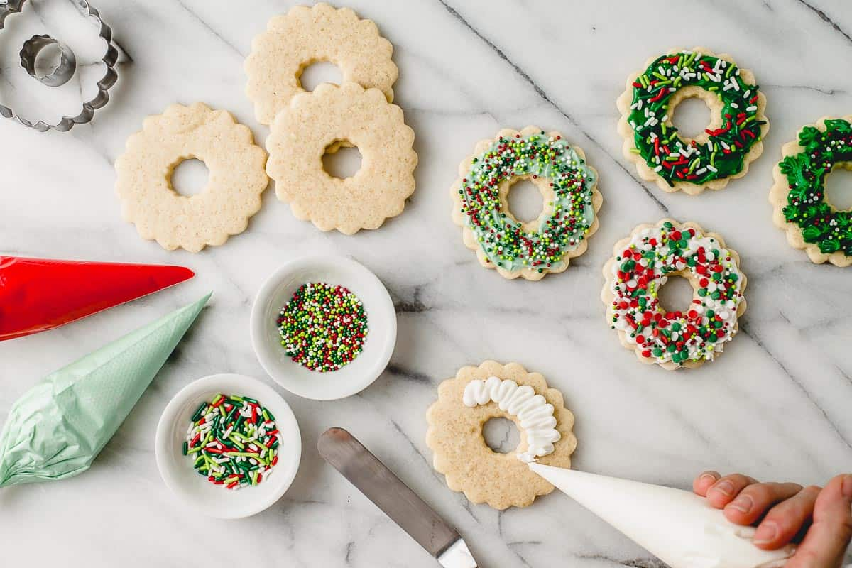 A woman decorating sugar cookies with frosting and sprinkles.