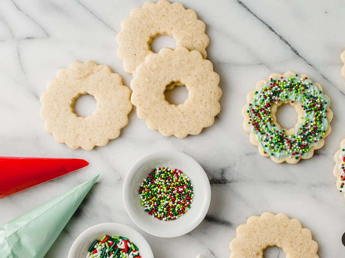 Baked cookies, bags of frosting and sprinkles to decorate with on a table.